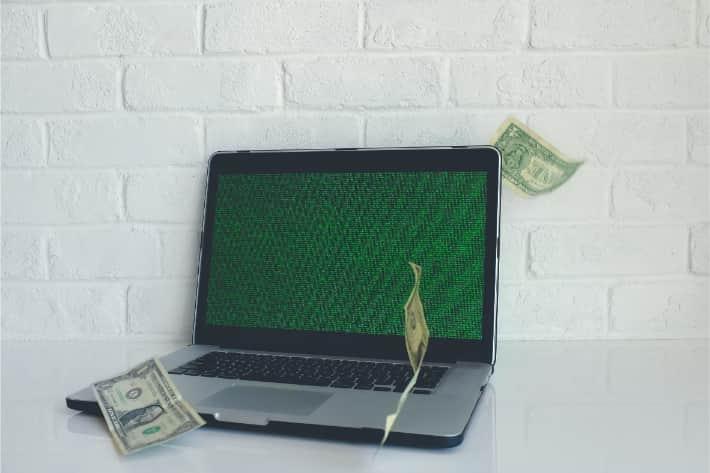 Gehackte laptop met vallende Amerikaanse dollarbiljetten