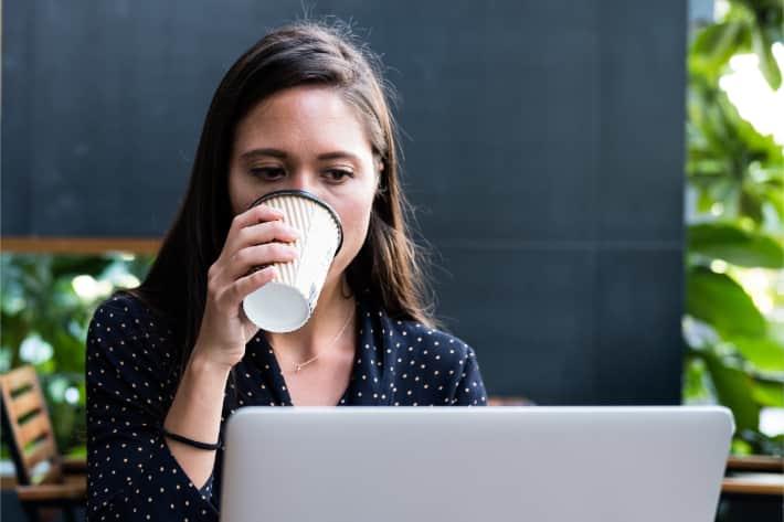 Vrouw surft op laptop en drinkt koffie